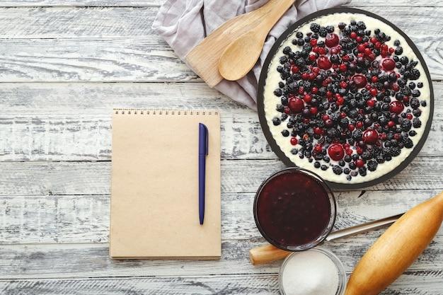 Torta di frutti di bosco con stoviglie e ricetta mockup sul tavolo di legno bianco