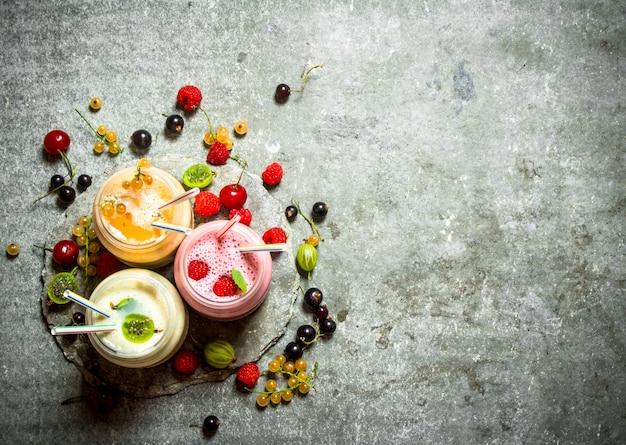 Frullato di frutti di bosco a base di lamponi, ribes e uva spina. su uno sfondo di pietra.