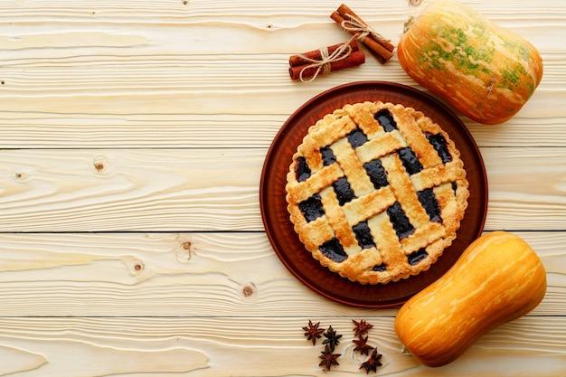 Berry torta crostata e zucca arancione sul tavolo di legno