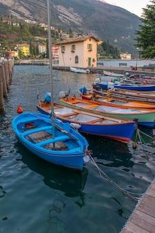 Ormeggio con barche nella città di riva del garda. italia. molo a riva del garda.