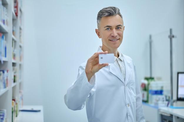 Scelta migliore. fiducioso uomo sorridente in camice bianco medico che lavora alla cassa della farmacia che mostra la carta di luce