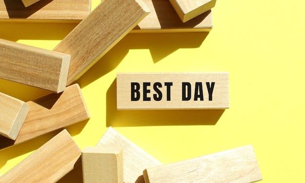 Best day testo scritto su blocchi di legno su sfondo giallo. concetto di affari