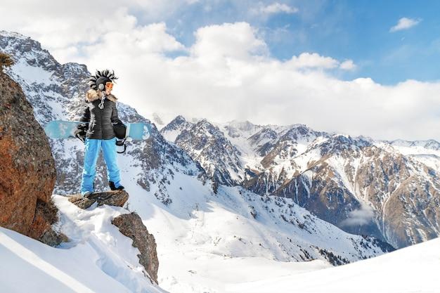 La migliore foto epica di sport invernali estremi con snowboarder giovane donna con cappello mohawk in montagne rocciose