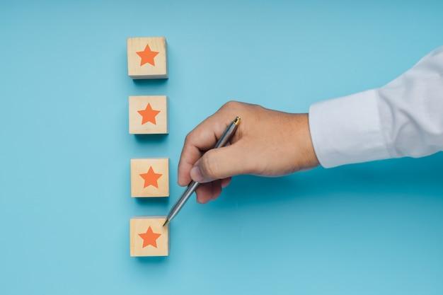 I migliori servizi aziendali eccellenti che valutano il concetto di esperienza del cliente di cinque stelle su blocco di legno su sfondo blu