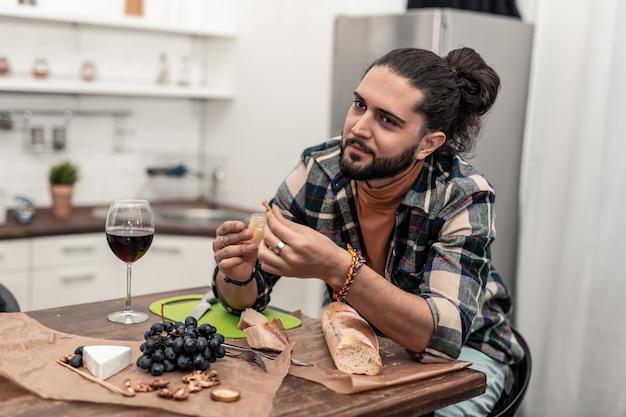 Miglior cibo. un bell'uomo positivo che ha un'ottima cena mentre si gode il riposo a casa