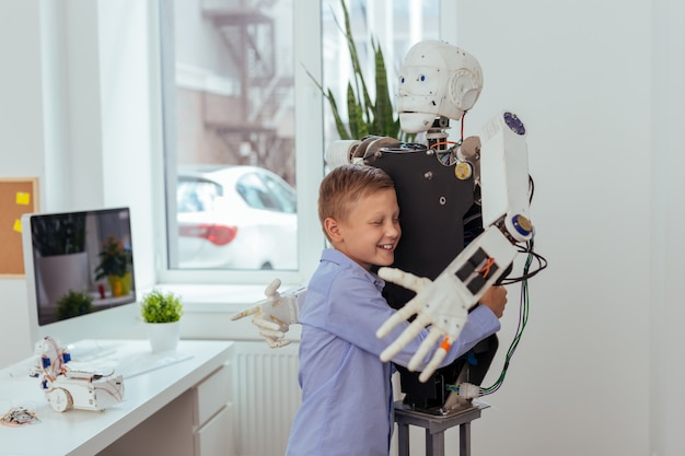 Migliore amico. ragazzo felice allegro che sorride mentre abbraccia un robot