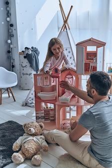 Migliori amici. padre e figlia giocano insieme con una casa delle bambole mentre
