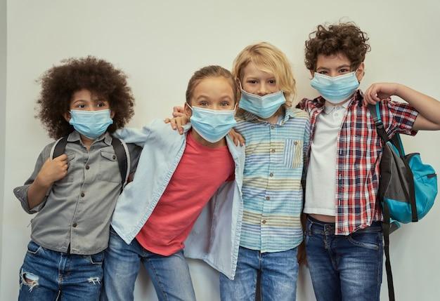 Migliori amici quattro adorabili bambini diversi che indossano maschere protettive che guardano la telecamera in posa