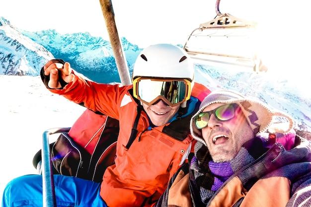 I migliori amici si divertono a fare selfie in seggiovia con l'attrezzatura da snowboard sulla stazione sciistica di montagna