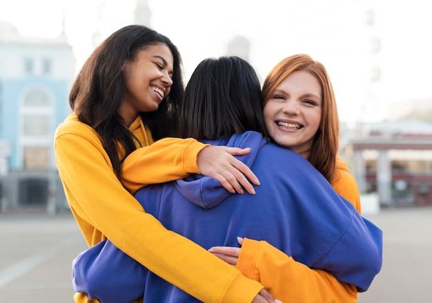 Migliori amici che abbracciano all'aperto
