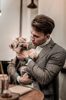 I migliori amici. un uomo che si prende cura del piccolo cane divertente