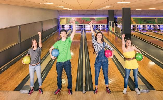 Migliori amici in posa in posizione di vittoria in pista da bowling guardando la fotocamera