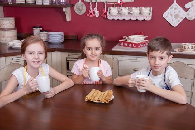 I migliori piccoli amici che riposano in cucina e tengono le tazze in mano e bevono tè e guardano