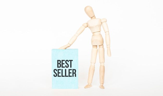 Concetto best seller. burattino di legno tocco blocco di legno verde. concetto di affari
