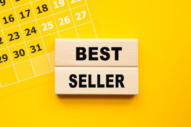 Scritta best seller su cubi, penna gialla su fondo giallo. una soluzione brillante per il concetto di business, finanziario, marketing