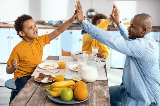 La migliore squadra. allegra famiglia monoparentale seduta al tavolo della cucina e che si danno il cinque a vicenda mentre si fa colazione
