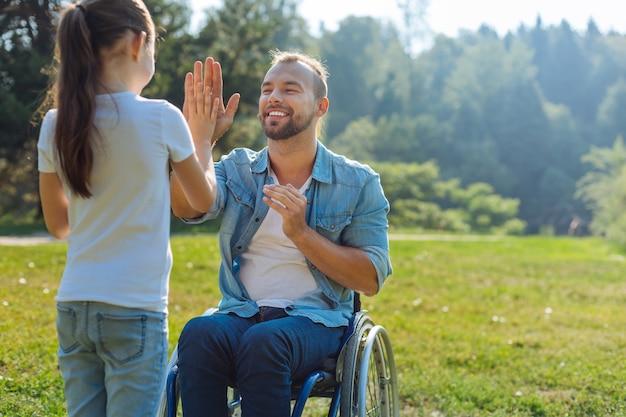 La migliore squadra. adorabile bambina che dà il cinque al suo affascinante padre con difficoltà motorie mentre trascorre il fine settimana nel parco