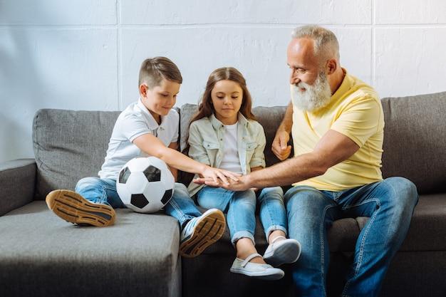 La migliore squadra. adorabile bambina seduta sul divano accanto a suo fratello e suo nonno e li guarda tenersi per mano mettendoli mano nella mano