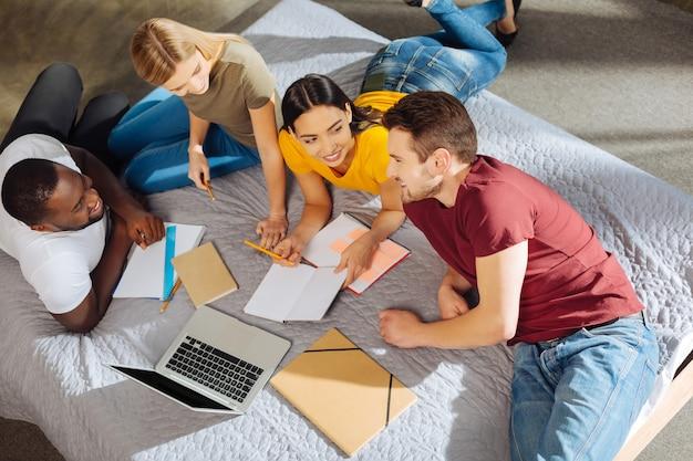 La migliore squadra. vista dall'alto di quattro simpatici studenti entusiasti e attraenti che si guardano l'un l'altro mentre sorridono e escogitano un piano