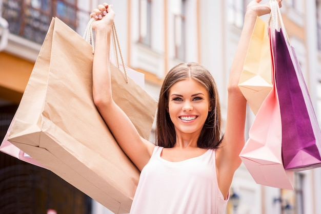 La migliore terapia è fare shopping. attraente giovane donna che tiene le borse della spesa e sorride mentre sta in piedi all'aperto