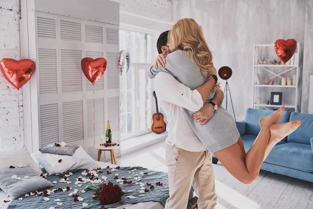 Il miglior san valentino. bella giovane coppia che si abbraccia e sorride mentre sta in piedi nella camera da letto piena di palloncini