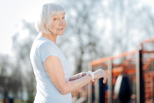 Miglior orologio. felice vecchia donna che indossa un fitness tracker mentre si esercita all'aria aperta