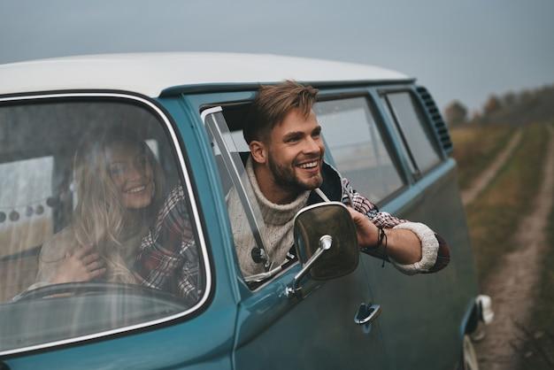 Il modo migliore per fuggire dalla città. bel giovane che si sporge dal finestrino del furgone e sorride mentre è seduto sui sedili del passeggero anteriore insieme alla fidanzata