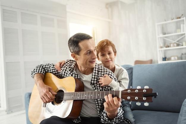 Miglior weekend. bell'uomo dai capelli scuri felice che sorride e che suona la chitarra e suo figlio che lo abbraccia