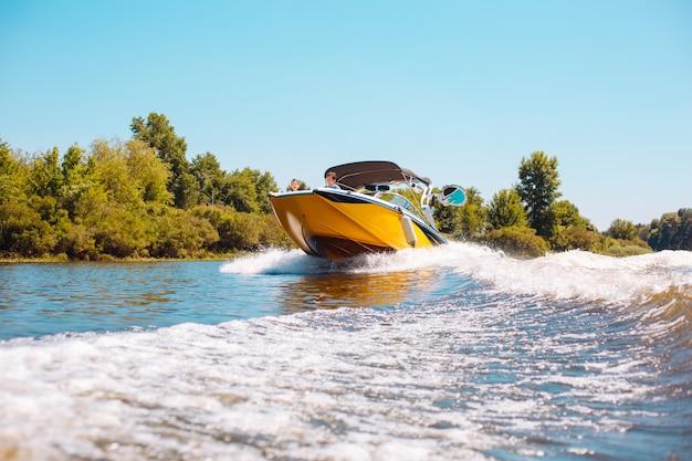 Miglior weekend. giovane famiglia felice che naviga un motoscafo lungo il fiume mentre due bambini sbirciano dalla prua della barca