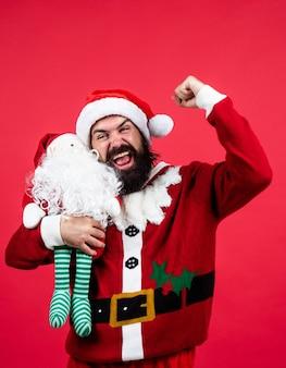 Auguri. saldi natalizi stagionali. uomo maturo barbuto indossa il costume rosso di babbo natale con il giocattolo. pronto per la celebrazione. prepararsi per le vacanze invernali. divertimento di festa. buon anno. buon natale.