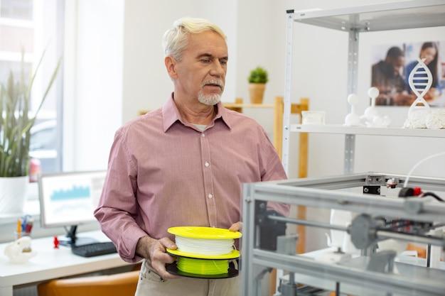 Miglior lavoratore. bello impiegato senior che trasporta due bobine di filamento e sta per inserirle in una stampante 3d