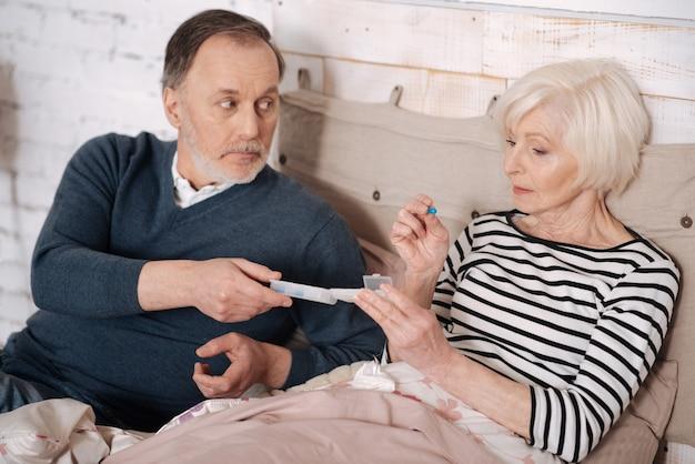 Per meglio. chiuda in su della signora ammalata invecchiata che prende la pillola dal suo marito anziano.