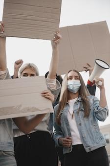 Per un futuro migliore gruppo di attivisti che danno slogan in un raduno uomini e donne caucasici che marciano