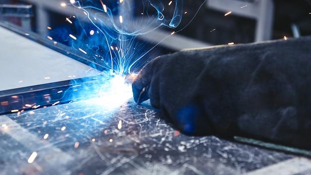 Il modo migliore per saldare. mano nella tenuta del guanto in acciaio per saldatura. saldature con saldatura ad arco di argon.