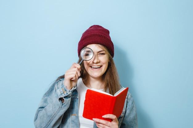 Una bella ragazza che sorride e mostra gesti con una lente d'ingrandimento e un libro in mano contro uno sfondo blu