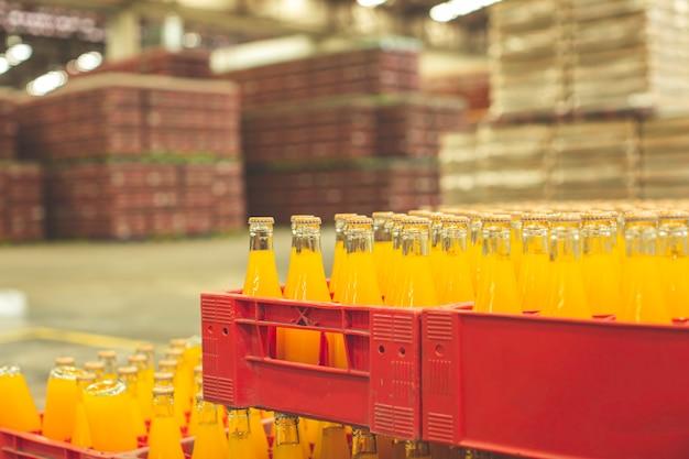 Interno della fabbrica di bevande. trasportatore che scorre con bottiglie per succhi di frutta o acqua.