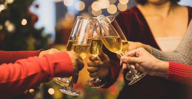 Bicchieri da bevanda momento tintinnante di allegre amiche sul maglione mentre divertiti a celebrare una relazione felice al delizioso evento della festa notturna di natale. aggiungi un po' di rumore per adattare l'immagine in stile vintage.