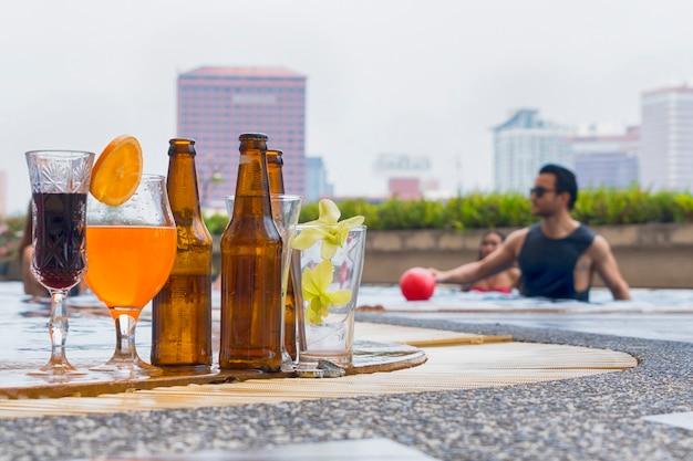 Bevande e succhi di frutta con cocktail esotici e bottiglia di birra allestita a bordo piscina con sfondo