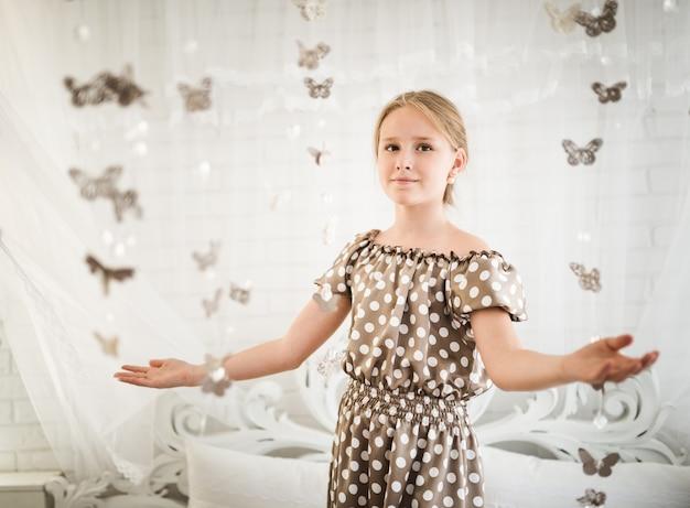 La bambina stregata in un vestito blu a pois gioisce di magia con le farfalle sognando di entrare in un fantastico mondo da favola