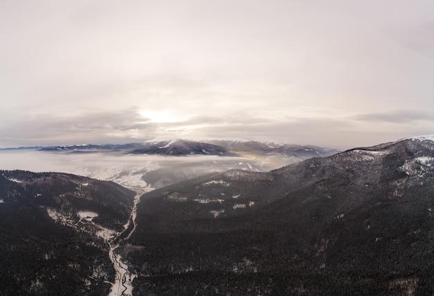 Vista ammaliante di splendide scogliere di montagna ricoperte di neve e nebbia in una nuvolosa giornata invernale. stazione sciistica. il concetto di turismo nei paesi del nord