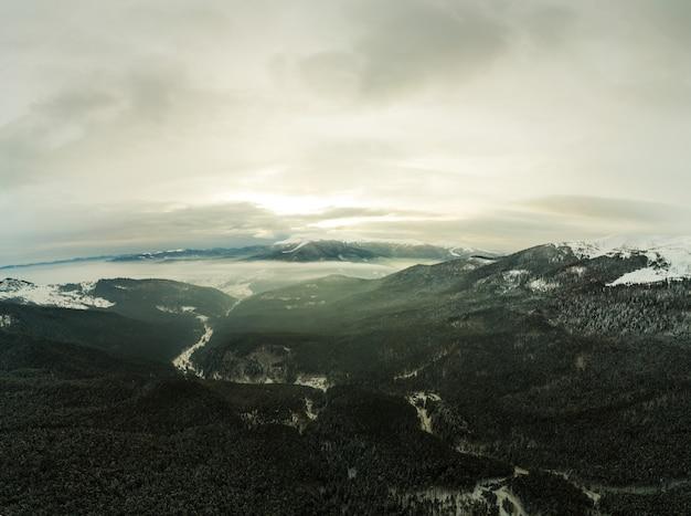 Vista ammaliante di bellissime scogliere di montagna ricoperte di neve e nebbia in una nuvolosa giornata invernale