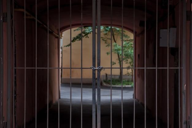 Oltre i cancelli in ferro battuto c'è un arco con luce e verde. cancelli chiusi. legato con catena metallica e lucchetto. cancello esterno di sfondo chiaro. concetto di immigrazione con frontiere chiuse