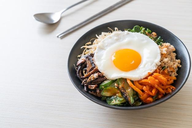 Bibimbap, insalata piccante coreana con riso e uovo fritto - stile di cucina tradizionalmente coreano