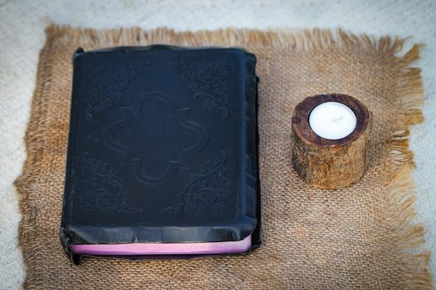 Bibbia e candela su un tovagliolo di tela.