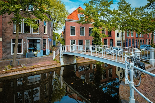 Bicicletta sul ponte e sul canale con auto parcheggiate lungo in via delft
