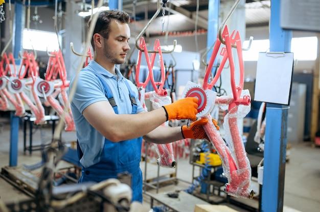 Fabbrica di biciclette, operaio detiene il telaio della bici per bambini rosa. meccanico maschio in uniforme installa parti di ciclo, catena di montaggio in officina