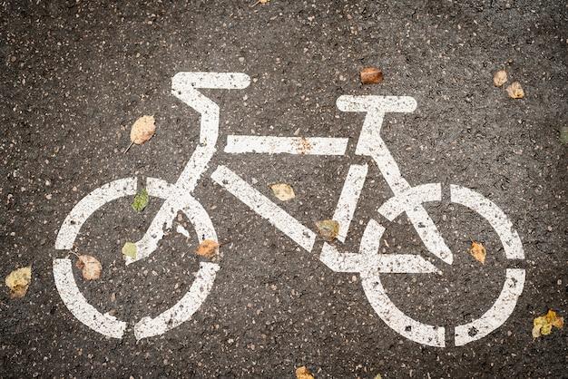 Pista ciclabile segno su asfalto con foglie gialle