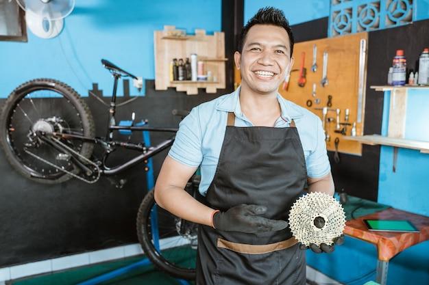 Un meccanico di biciclette in un grembiule che sorride tenendo una ruota libera con un gesto della mano che presenta qualcosa