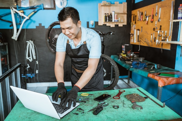 Un meccanico di biciclette in un grembiule che indossa guanti si eccita mentre usa un laptop per cercare parti