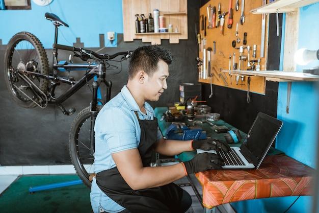 Un meccanico di biciclette in un grembiule che indossa guanti seduto mentre usa un laptop per cercare pezzi di ricambio